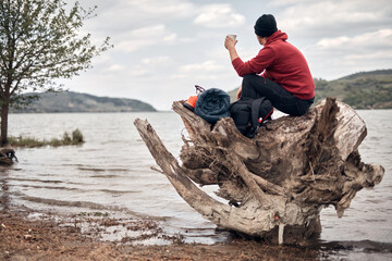 Obraz Hiker camping in nature on a river shore. - fototapety do salonu