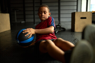 Concentrated African little boy in sportswear sitting on floor in gym doing twists using medicine ball, twisting torso to sides, strengthening core muscles. Fitness, equipment and body shape