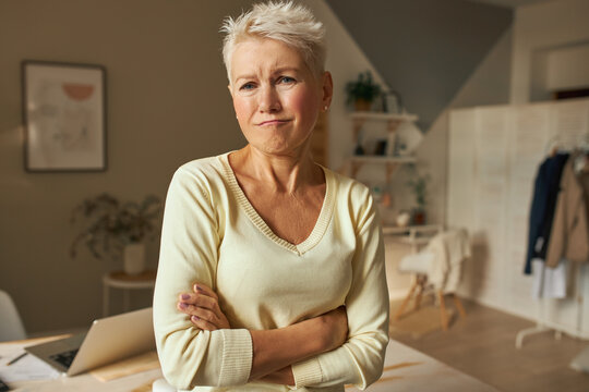 Portrait of displeased disappointed middle aged woman with blonde short hair making grumpy unhappy grimace, crossing arms on her chest feeling bored at home alone. Human emotions and feelings