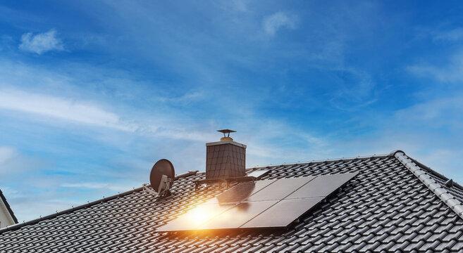 Hausdach mit schwarzen Dachziegeln und Photovoltaikanlage