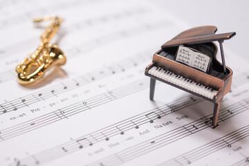 楽譜を背景にしたグランドピアノとサックス