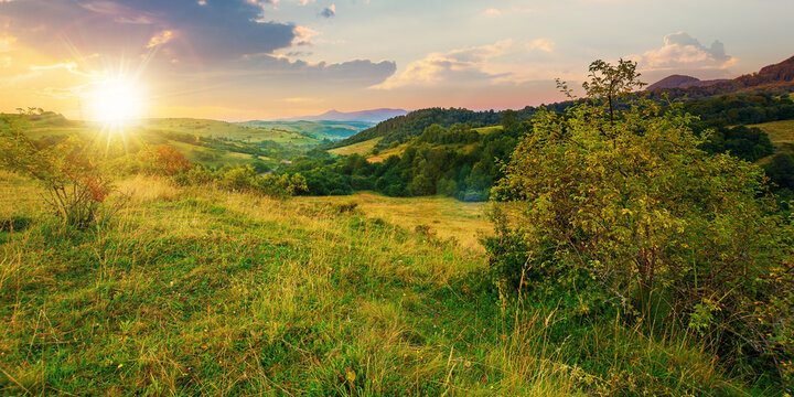 mountainous rural landscape at sunset. beautiful scenery with forests, hills and meadows in evening light. ridge with high peak in the distance. village in the distant valley