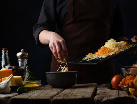 Cooking cheese soup. The cook prepares cheese soup. Mixes ingredients in a saucepan: several types of cheese, carrots. On the table - onion, oil, salt, tomatoes. Wooden table. Dark background.