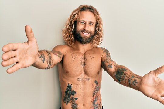 Handsome man with beard and long hair standing shirtless showing tattoos looking at the camera smiling with open arms for hug. cheerful expression embracing happiness.
