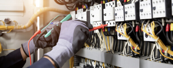 Obraz Electrician engineer tests electrical installations and wires on relay protection system. Adjustment of scheme of automation and control of electrical equipment. - fototapety do salonu
