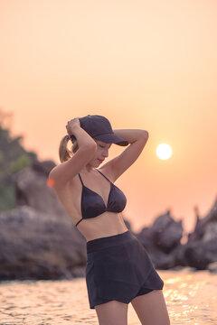 Woman in the black bikini posing on the rock beach in the ocean on the orange sunset background.