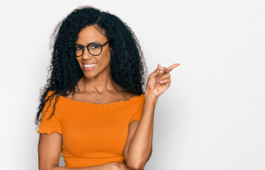 Middle age african american woman wearing casual clothes and glasses with a big smile on face, pointing with hand and finger to the side looking at the camera.
