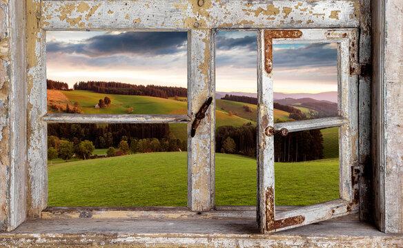 Blick aus einem Holzfenster in die Landschaft