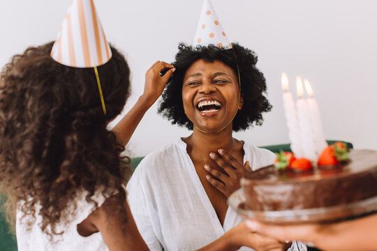 Cheerful woman celebration her birthday with daughter at home