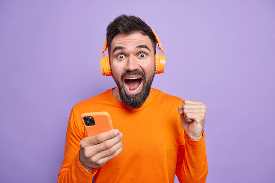 Overjoyed unshaven man celebrates excellent news clenches fist holds mobile phone uses wireless headphones for listening music enjoys good sound wears orange jumper isolated over purple background