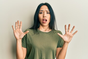 Young hispanic girl wearing casual t shirt afraid and terrified with fear expression stop gesture with hands, shouting in shock. panic concept.