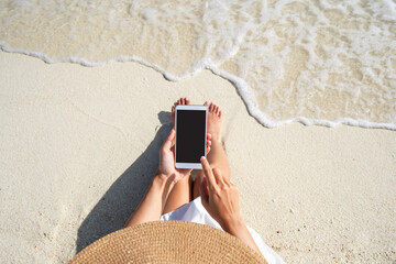 Fototapeta Young woman using mobile phone at beautiful tropical white sand beach with wave foam and transparent sea, Summer vacation and Travel concept with copy space obraz