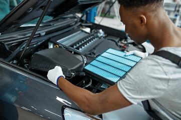 Obraz Male mechanic changes air filter, car service - fototapety do salonu