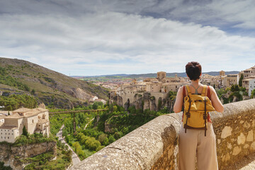 Fototapeta Horizontal view of unrecognizable woman with backpack on holidays looking at the ancient spanish city of Cuenca. Travel and holidays concept in european cities. obraz