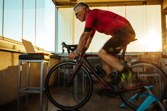 Senior man cycling bike during home online workout