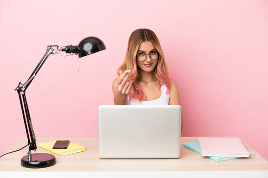 Young student woman in a workplace with a laptop over pink background making money gesture