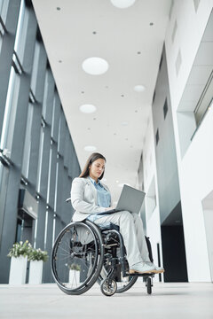 Vertical low angle portrait of successful businesswoman in wheelchair using laptop in office lobby, copy space
