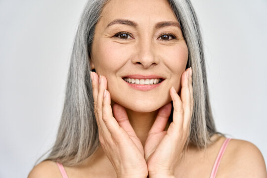 Closeup portrait of gorgeous happy middle aged mature asian woman, senior older 50 year lady looking at camera touching her face isolated on white. Ads of lifting anti wrinkle skin care, spa.
