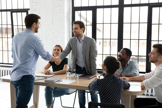 Happy millennial business team welcoming new employee, HR manager getting acquainted with colleague. Group leader shaking partner hand over meeting table, start negotiation, thanking for expert help