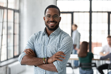 Fototapeta Portrait of happy African American small business owner posing with hands folded. Millennial black male team leader smiling, looking at camera, employees working in modern office behind. Head shot obraz