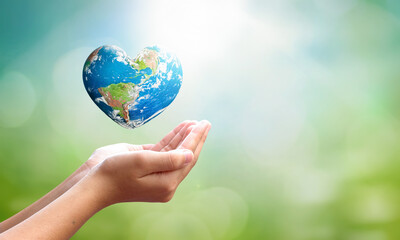Fototapeta World environment day concept: man opens palms and drags heart shaped earth globe over blurred blue sky and water background. Elements of this image furnished by NASA obraz