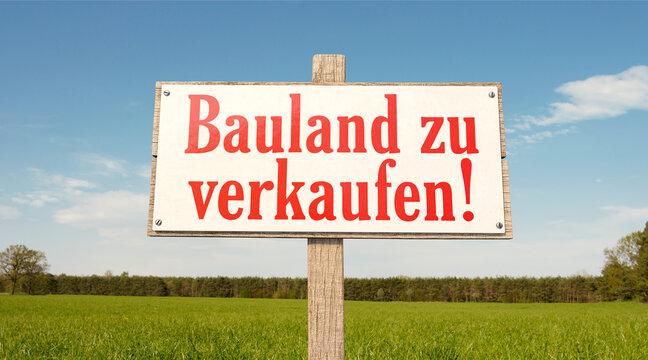Schild auf der grünen Wiese: Bauland zu verkaufen!
