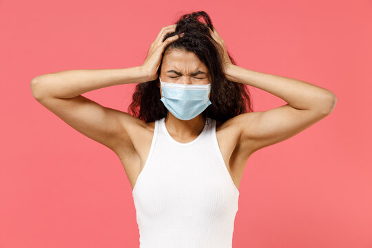 Young troubled stress african american woman in casual white tank shirt sterile face mask ppe to safe from coronavirus virus covid-19 flu on lockdown quarantine hold head isolated on pink background