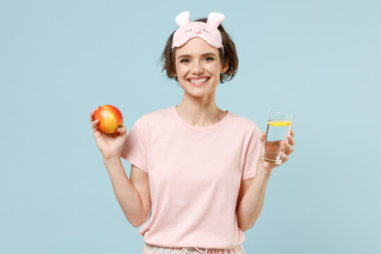 Young fun woman in pajamas jam sleep eye mask rest relaxing at home hold apple fruit glass of water with lemon isolated on pastel blue background studio. Healthy vegeterian food night bedtime concept.