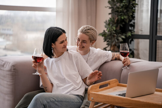 happy lesbian couple watching movie on laptop while holding glasses of red wine