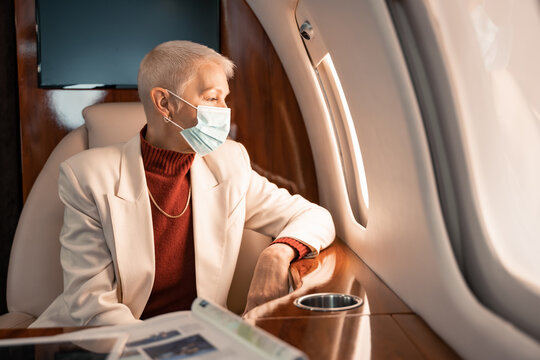 Businesswoman in medical mask looking at plane window near magazine and digital tablet