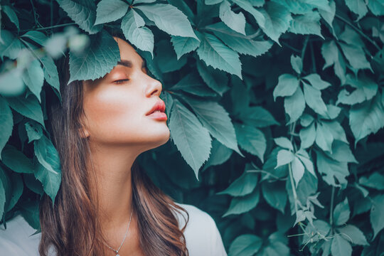 Beautiful fashion model girl enjoying nature, breathing fresh air in summer garden over Green leaves background. Harmony concept. Healthy beauty woman outdoor portrait
