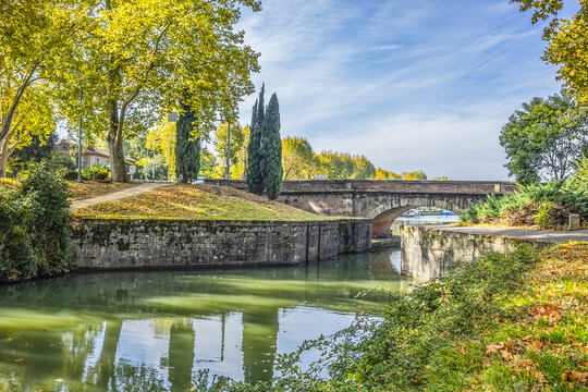 Beautiful autumn views of Canal du Midi (in XVII century - Royal Canal in Languedoc) in Toulouse and trees reflection in water. Toulouse, Haute-Garonne, France.