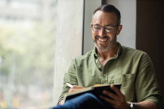 Mature man with beard, glasses writing in book sitting by sunny window