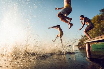Fototapeta Friends having fun enjoying a summer day swimming and jumping at the lake. obraz