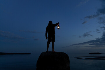 Fototapeta Man standing on the rock and holding old lantern outdoors near the sea at night.  Light and hope concept. obraz