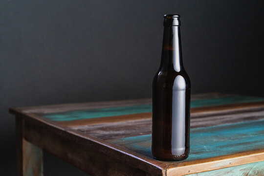 Dark glass bottle of alcoholic drink on painted square shaped wooden table at home