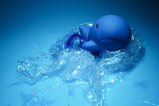 Arrangement of blue toy dolphin wrapped in plastic debris representing ocean environmental problems