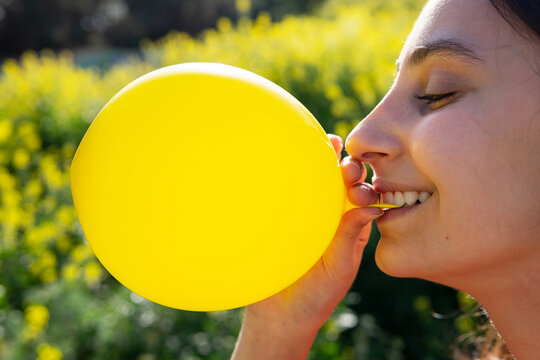 Crop female with bright balloon against blooming plants on sunny day