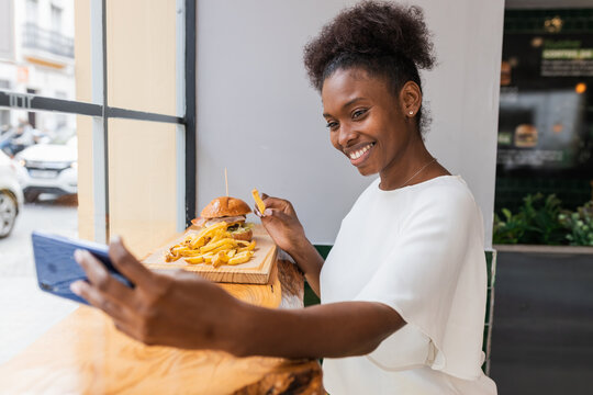 Side view joyful young African American female in white blouse enjoying delicious French fries and burger while taking selfie on smartphone in fast food restaurant