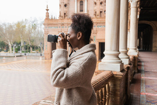 Side view young African American female photographer in warm coat taking pictures of historic city buildings on modern photo camera on early spring day