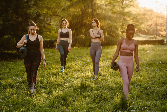 Confident fit multiracial female athletes walking with mat along lawn during training in summer park in evening