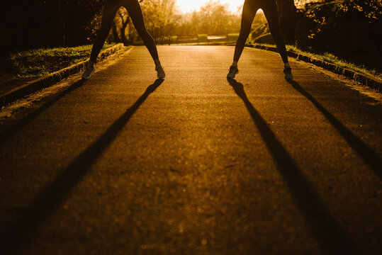 Crop anonymous female sportswomen standing on pathway in park during training at sundown in summer
