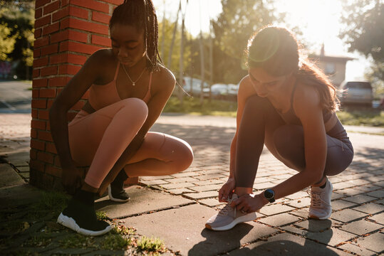 Young multiethnic female athletes tying shoelaces on footwear while squatting on urban pavement before training in back lit