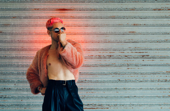 Young gay in modern sunglasses and stylish fur jacket with pink hair against gray wall