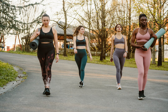 Company of multiracial female athletes in leggings and bra walking along street for training in summer park