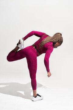 Black sportswoman in activewear training on white background