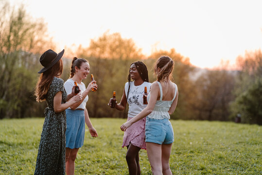 Anonymous best multiracial female friends with bottles of alcoholic drink looking at each other while speaking on lawn in evening