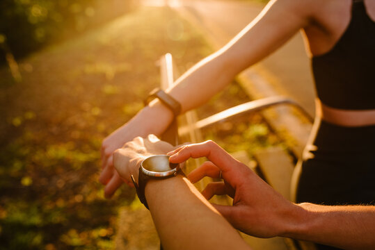 Crop unrecognizable female athlete checking pulse on smart watch while standing in park with anonymous athlete at sunset