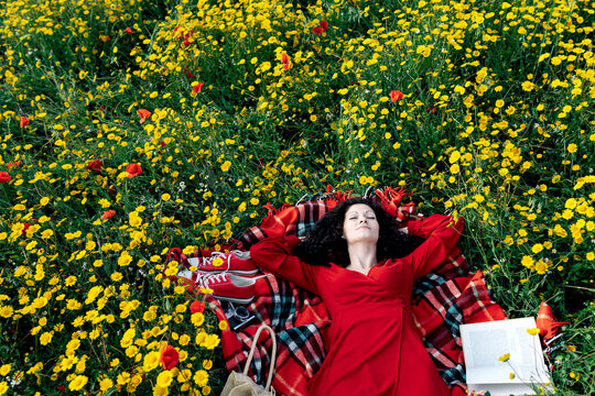 From above of female with eyes closed having a break from reading textbook on blanket with handbag among blossoming daisies during a spring summer day