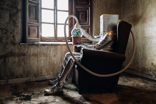 Side view unrecognizable person in silver costume with breathing apparatus and hose attached to potted plant sitting on chair in weathered abandoned house room